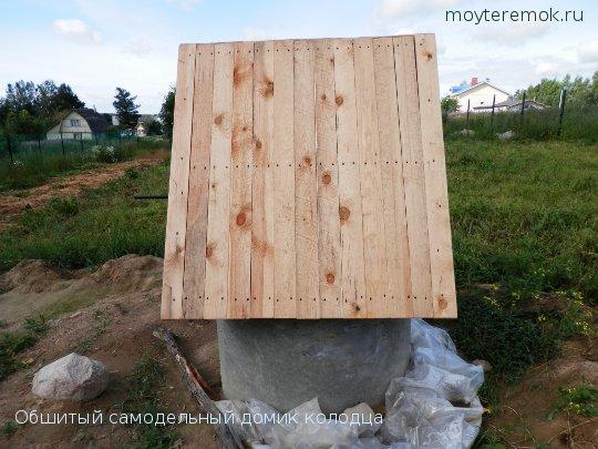 обшитый доской самодельный домик для колодца